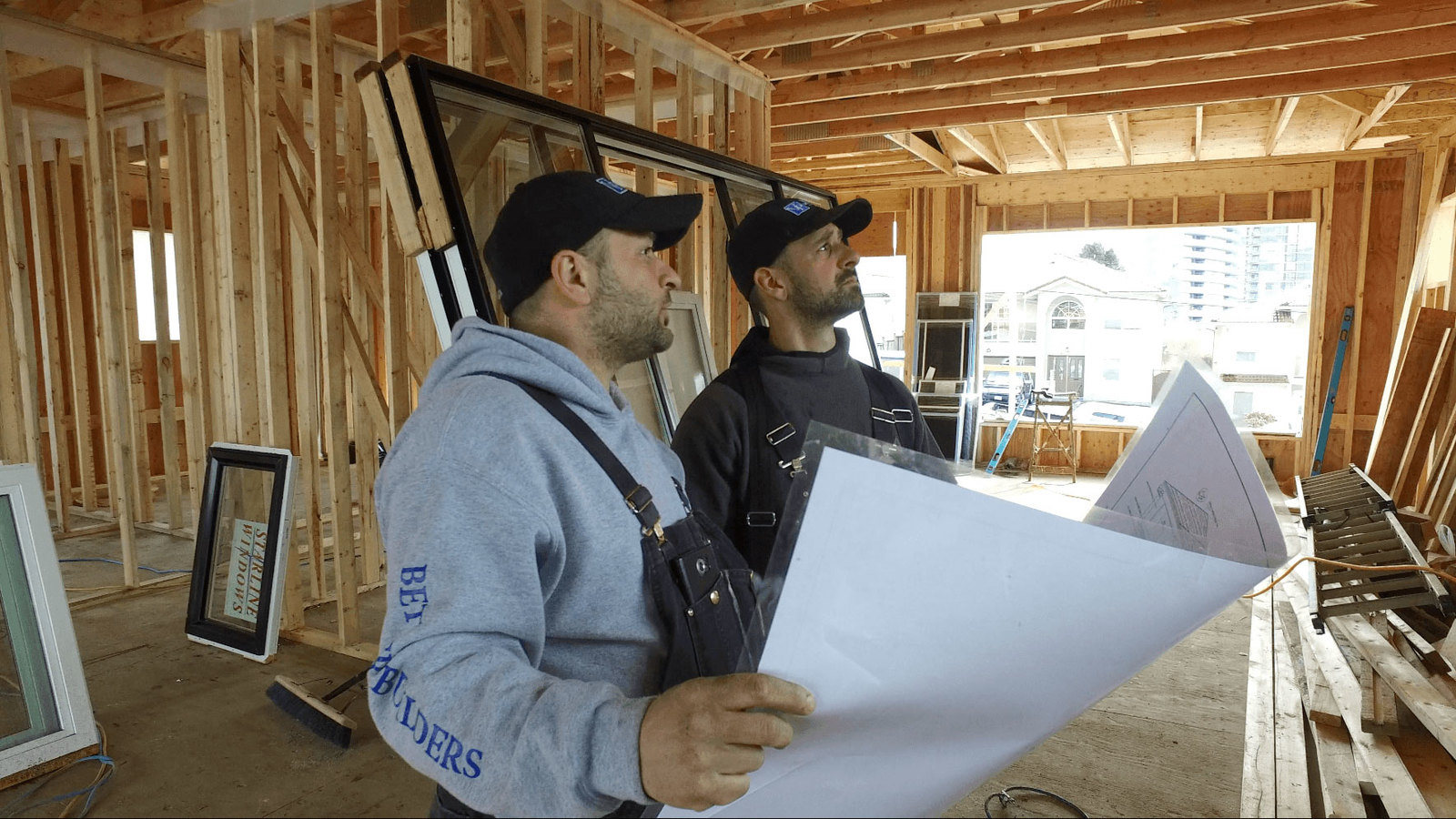 Two construction workers examine the plans of a construction site